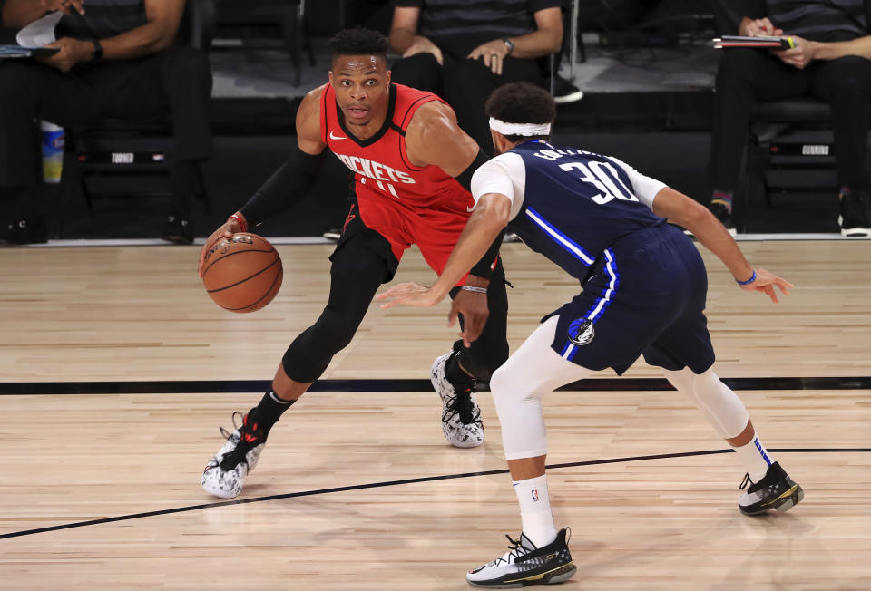 Houston Rockets' Russell Westbrook, left, dribbles against Dallas Mavericks' Seth Curry, right, during the first half of an NBA basketball game Friday, July 31, 2020, in Lake Buena Vista, Fla. (Mike Ehrmann/Pool Photo via AP)