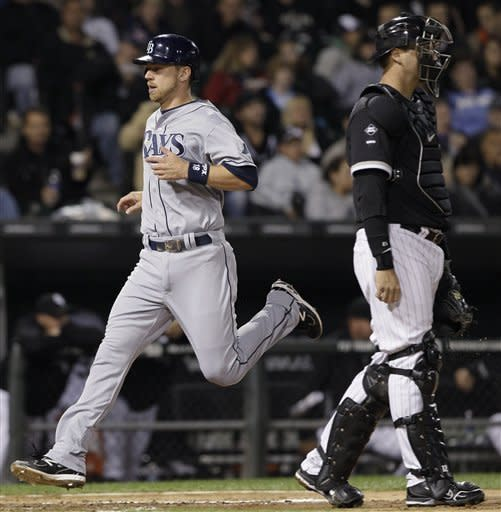 Tampa Bay Rays' Ben Zobrist, left, scores on a sacrifice fly hit by Carlos Pena as Chicago White Sox catcher A.J. Pierzynski looks to the field during the fourth inning of a baseball game in Chicago, Thursday, Sept. 27, 2012. (AP Photo/Nam Y. Huh)