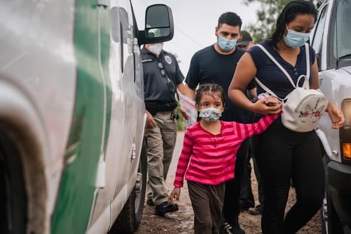 An immigrant family seeking asylum prepare to be taken to a border patrol processing facility after crossing into the US on 16 June, 2021 in La Joya, Texas. US Attorney General Merrick Garland has reversed two Trump-era asylum decisions. (Getty Images)