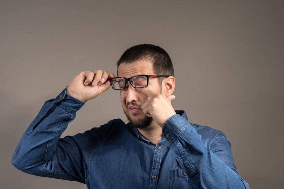 a gentleman with a beard scratching his eyes with glasses
