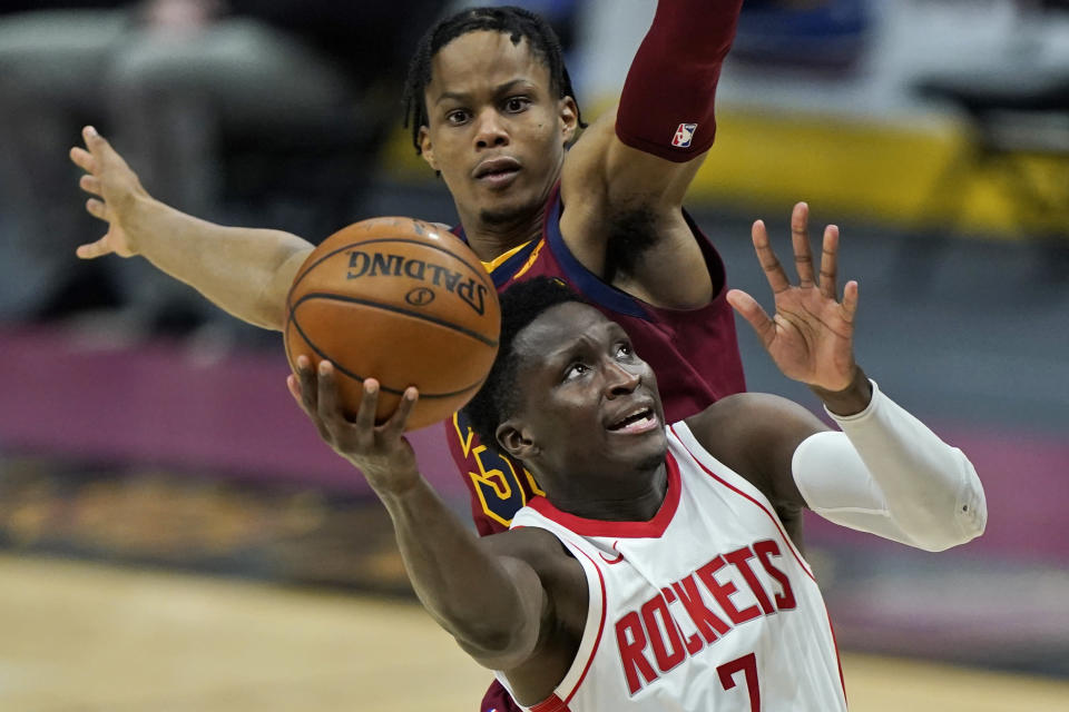 Houston Rockets' Victor Oladipo, front, drives to the basket against Cleveland Cavaliers' Isaac Okoro in the second half of an NBA basketball game, Wednesday, Feb. 24, 2021, in Cleveland. The Cavaliers won 112-96. (AP Photo/Tony Dejak)