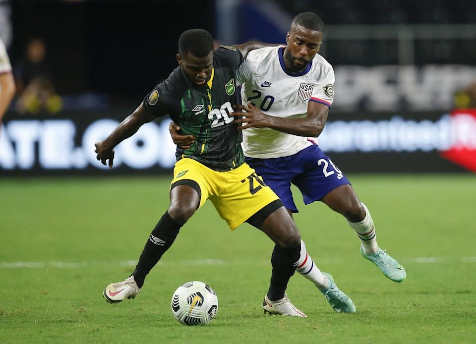 Jamaica's Kemar Lawrence, left, and U.S. defender Shaq Moore battle for the ball on July 25 in Arlington, Texas.