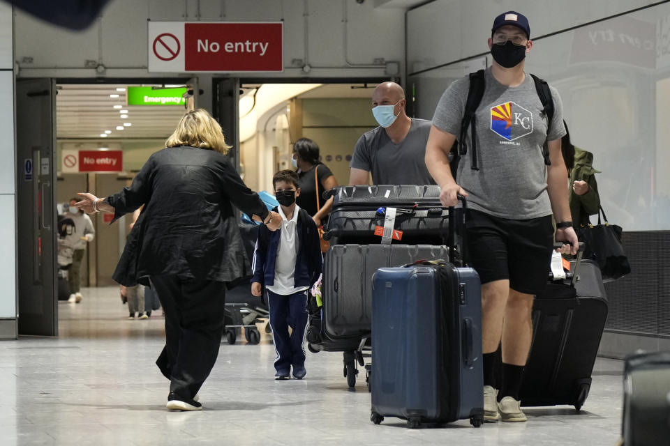 A woman runs to greet a child as passengers arrive at Terminal 5 of Heathrow Airport in London, Monday, Aug. 2, 2021. Travelers fully vaccinated against coronavirus from the United States and much of Europe were able to enter Britain without quarantining starting today, a move welcomed by Britain's ailing travel industry. (AP Photo/Matt Dunham)