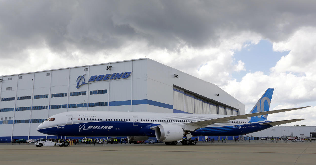 FILE - In this Friday, March 31, 2017, file photo, Boeing employees stand near the new Boeing 787-10 Dreamliner at the company's facility in South Carolina after conducting its first test flight at Charleston International Airport in North Charleston, S.C. Orders to U.S. factories rose in February amid a surge in demand for commercial aircraft, but a key category that tracks business investment spending slipped for the first time in five months. (AP Photo/Mic Smith, File)