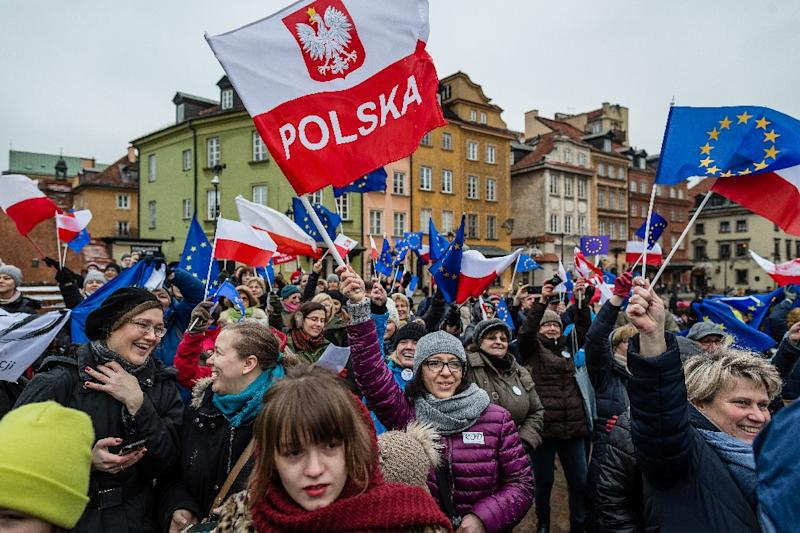 People wave European and Polish flags during a protest against a new media law in the center of Warsaw on January 9, 2016