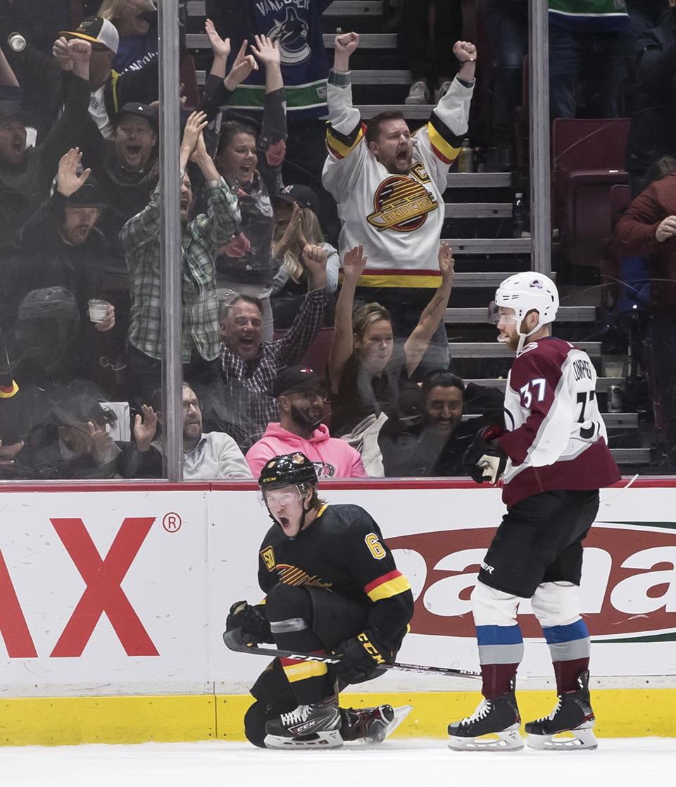 Vancouver Canucks' Brock Boeser, left, celebrates his tying goal in front of Colorado Avalanche's J.T. Compher during the third period of an NHL hockey game Saturday, Nov. 16, 2019, in Vancouver, British Columbia. (Darryl Dyck/The Canadian Press via AP)