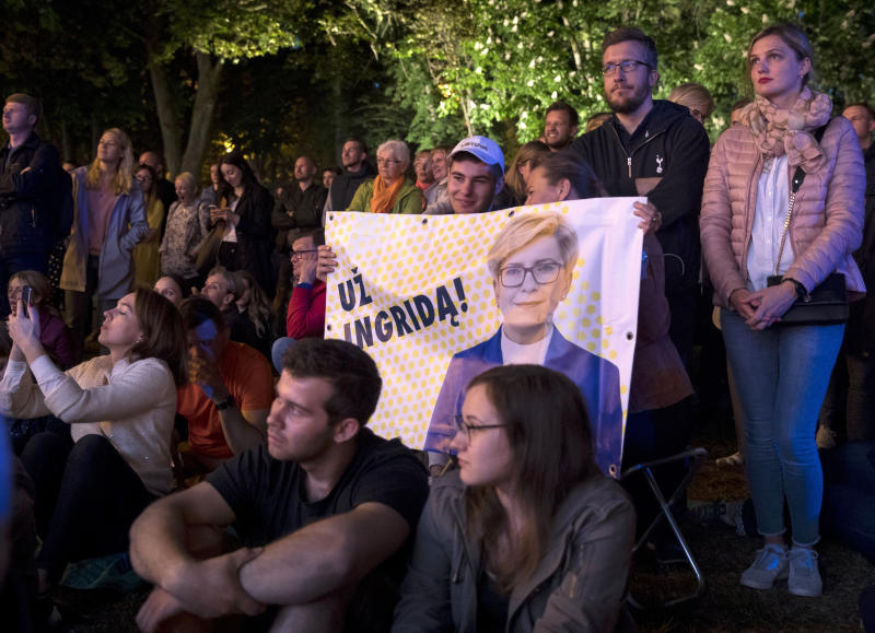People hold posters with an image of presidential candidate Ingrida Simonyte during debates between two candidates, Economist Gitanas Nauseda and former Finance Minister Ingrida Simonyte, at the S. Daukanto Square, in front of the Presidential Palace in Vilnius, Lithuania, Friday, May 24, 2019. Nauseda and Simonyte held the top two spots in returns from Lithuania's presidential election Sunday, May 26 and appeared headed to a runoff ballot later this month to choose a successor to incumbent Dalia Grybauskaite. (AP Photo/Mindaugas Kulbis)
