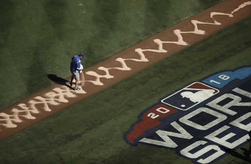 A groundskeeper puts dirt down the first base line before Game 3 of the World Series baseball between the Boston Red Sox and Los Angeles Dodgers on Friday, Oct. 26, 2018, in Houston. (AP Photo/Jae C. Hong)