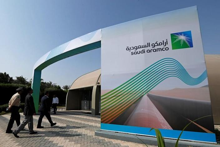 Logo of Aramco is seen as security personnel walk before the start of a press conference by Aramco at the Plaza Conference Center in Dhahran