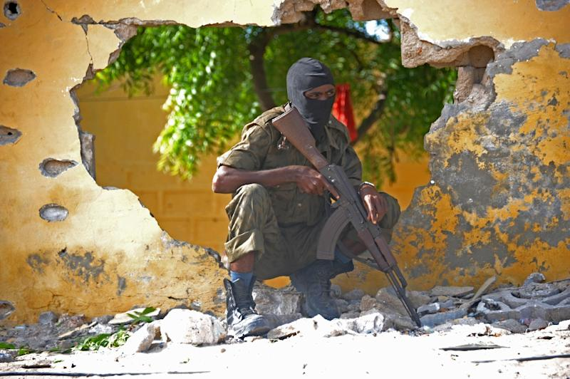 A Somali soldier stands guard next to the site where Al Shebab militants carried out a suicide attack against a military intelligence base in Mogadishu on June 21, 2015 (AFP Photo/Mohamed Abdiwahab)