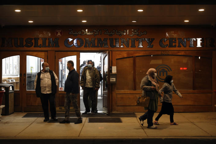 "Muslims exit Chicago's Muslim Community Center after an evening prayer called ""tarawih"" as others pass by during the first evening of the holy fasting month of Ramadan at Chicago's Muslim Community Center on Monday, April 12, 2021. (AP Photo/Shafkat Anowar)"