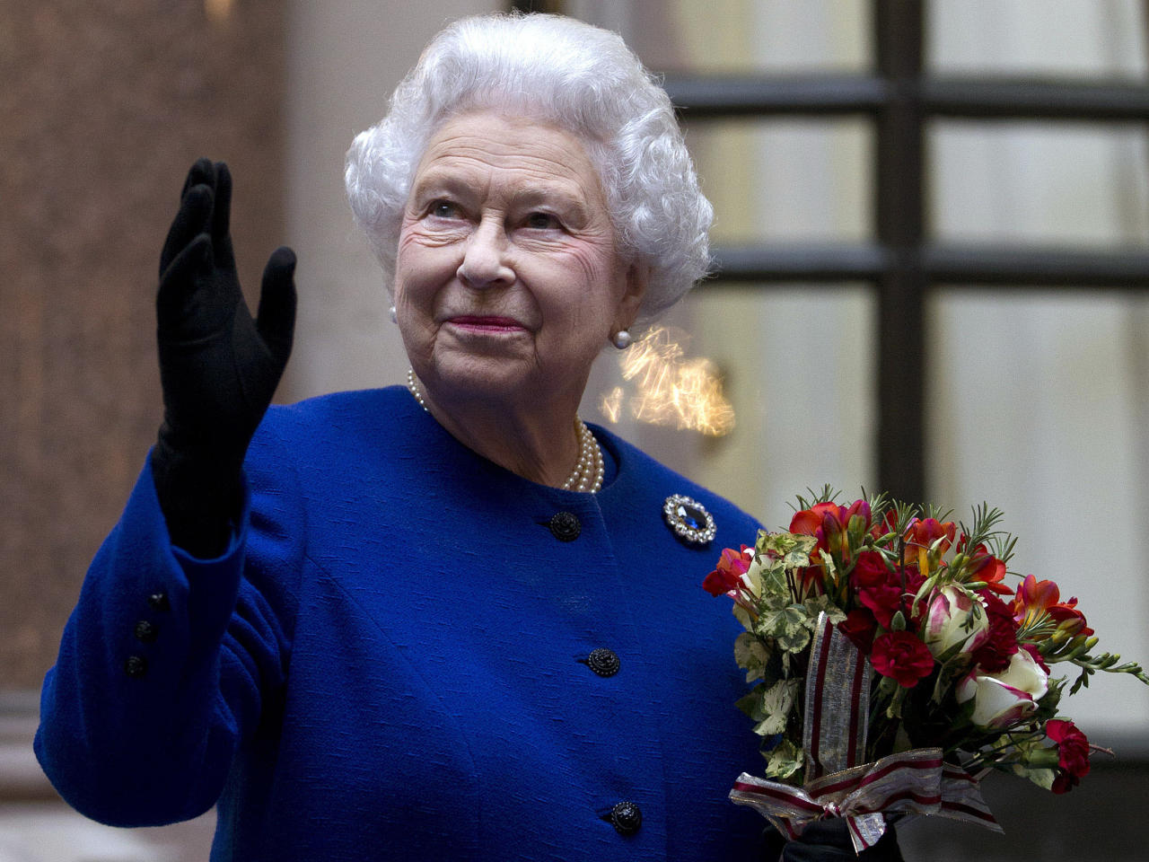 FILE - In this Tuesday, Dec. 18, 2012 file photo, Britain's Queen Elizabeth II looks up and waves to members of staff of The Foreign and Commonwealth Office as she ends an official visit which is part of her Jubilee celebrations in London. Queen Elizabeth has been taken to the King Edward VII hospital in central London suffering from gastroenteritis, Sunday, March 3, 2013. A palace spokesman said she was expected to stay in hospital for two days and all engagements for this week will be either postponed or cancelled.(AP Photo/Alastair Grant Pool, file)