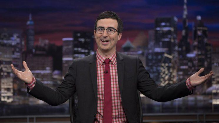 John Oliver in a red plaid shirt and red tie