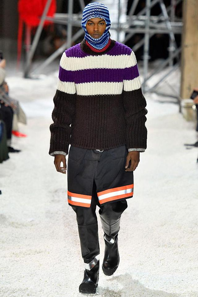 <p>A model wears a balaclava, striped sweater, and black safety skirt over his trousers with black boots at the Calvin Klein fall 2018 show. (Photo: Getty Images) </p>