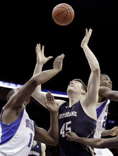 Notre Dame's Jack Cooley (45) competes for a loose ball against Seton Hall's Herb Pope, left, and Fuquan Edwin during the second half of an NCAA college basketball game, Wednesday, Jan. 25, 2012, in Newark, N.J. Notre Dame won 55-42. (AP Photo/Julio Cortez)