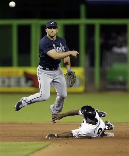 Atlanta Braves' Dan Uggla (6) makes the throw to first after tagging out Miami Marlins' Juan Pierre (9) to get Placido Polanco out during the eighth inning of a baseball game in Miami, Monday, April 8, 2013. The Braves won 2-0. (AP Photo/J Pat Carter)