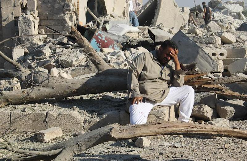A Syrian man cries as he sits on the rubble of a building following a reported barrel-bomb attack by Syrian government forces on August 11, 2014 in the northern Syrian city of Aleppo (AFP Photo/Baraa al-Halabi )
