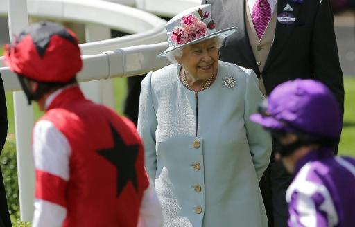 Britain's Queen Elizabeth II (C) reacts as jockeys and horses parade in the ring on the second day of the Royal Ascot horse racing meet, in Ascot, west of London, on June 20, 2018. The five-day meeting is one of the highlights of the horse racing calendar. Horse racing has been held at the famous Berkshire course since 1711 and tradition is a hallmark of the meeting. Top hats and tails remain compulsory in parts of the course while a daily procession of horse-drawn carriages brings the Queen to the course