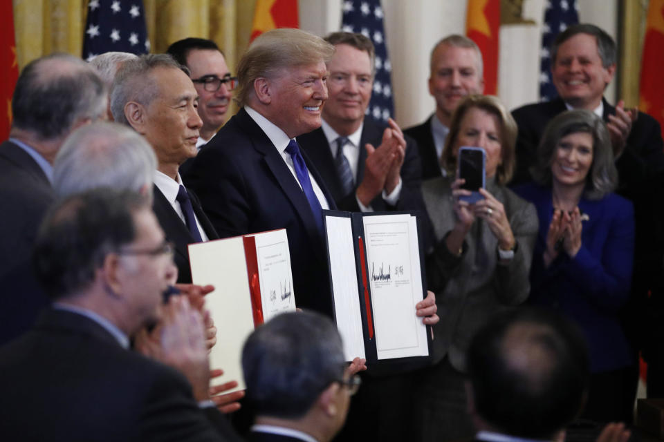 President Donald Trump, center, and Chinese Vice Premier Liu He, left, hold the U.S. China Trade Agreement after signing it in the East Room of the White House, Wednesday, Jan. 15, 2020, in Washington. (AP Photo/Steve Helber)