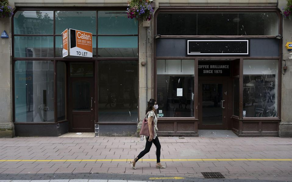 A woman wearing a surgical face mask walks passed closed shops