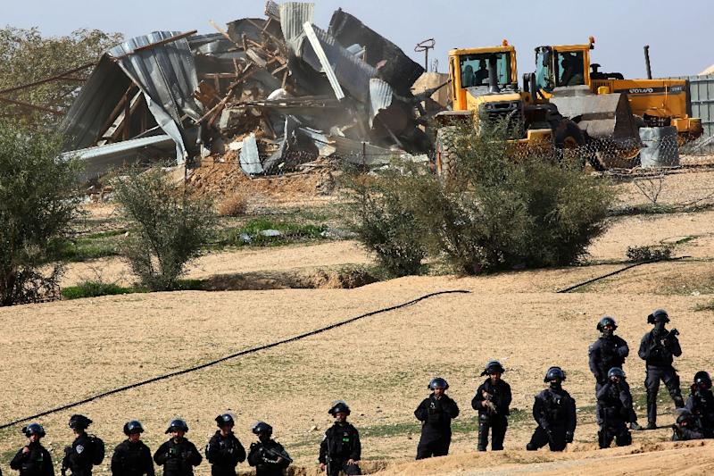 Israeli policemen stand guard as bulldozers demolish homes in the Bedouin village of Umm al-Hiran, which is not recognized by the Israeli government, near the southern city of Beersheba, in the Negev desert, on January 18, 2017 (AFP Photo/MENAHEM KAHANA)