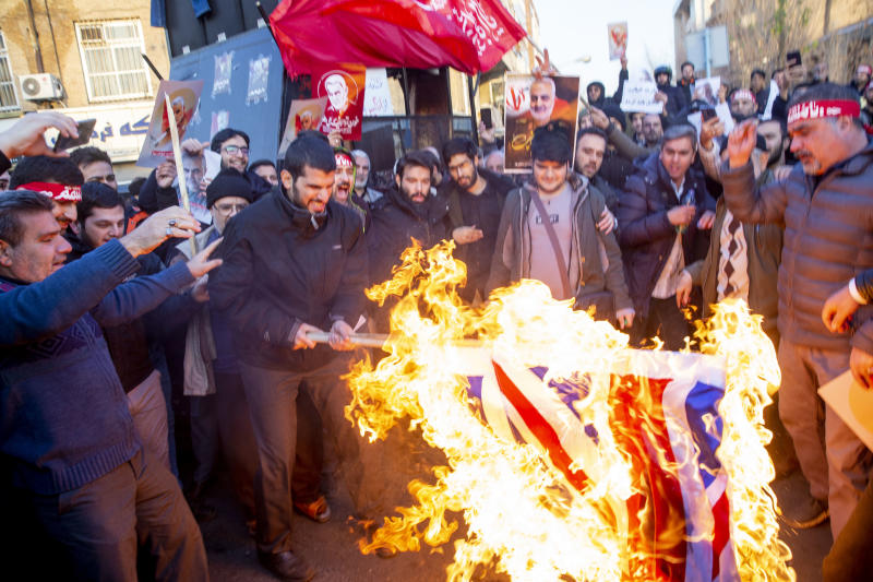 TEHRAN, IRAN - JANUARY 12: Protesters chant slogans and hold up posters of Gen. Qassem Soleimani while burning representations of British and Israeli flags, during a demonstration in front of the British Embassy on January 12, 2020 in Tehran, Iran. A candlelight vigil held late on Saturday in Tehran, to remember the victims of the Ukrainian plane crash, turned into a protest with hundreds of people chanting against the country's leaders including Supreme Leader Ayatollah Ali Khamenei and police dispersing them with tear gas. Police briefly detained the British ambassador to Iran, Rob Macaire, who said he went to the Saturday vigil without knowing it would turn into a protest. (Photo by Majid Saeedi/Getty Images)