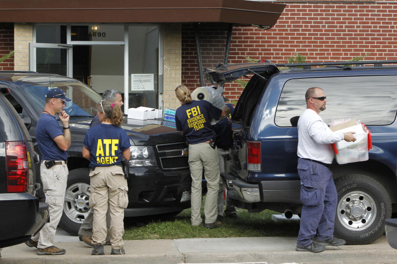 Federal agents unload material to collect evidence at the apartment house of shooting suspect James Eagen Holmes. Federal agents began collecting evidence from the apartment after clearing it of booby traps. in Aurora, Colo., Saturday, July 21, 2012. Holmes has been charged in the shooting at an Aurora theatre early Friday that killed twelve people and injured 59.(AP Photo/Ed Andrieski)