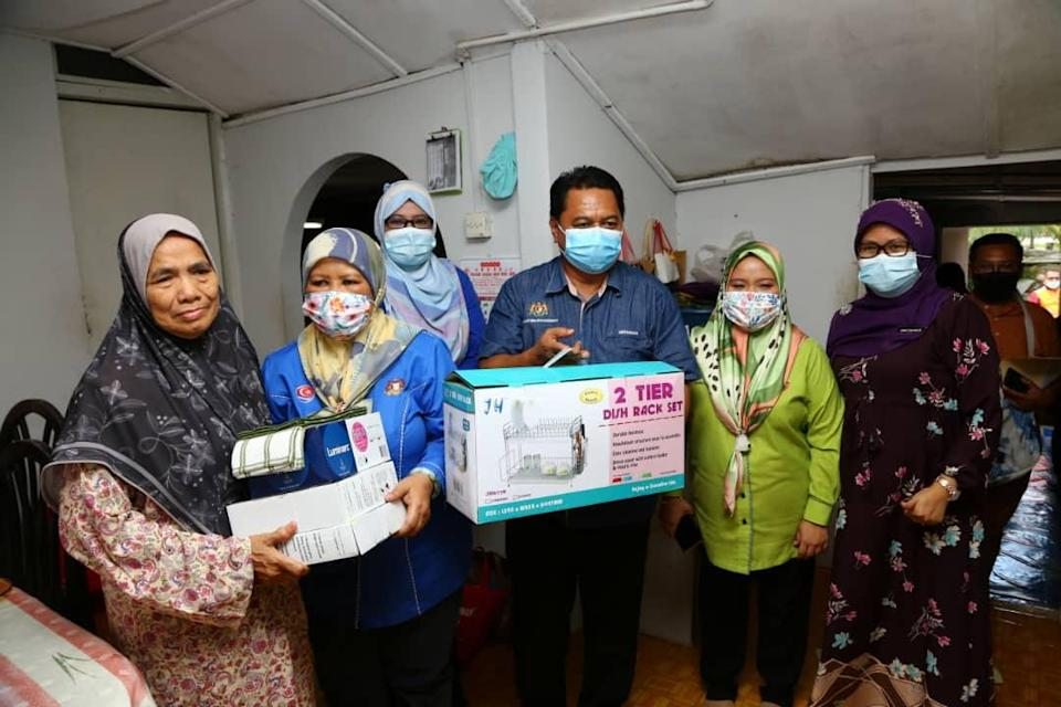 Johor Women, Family and Community Development Committee chairman Zaiton Ismail (second from left) and Johor Welfare Department director Mohamad Hapil (centre) hand over donations to Azizah Omar (left) at her house in Johor Baru. — Picture by Ben Tan