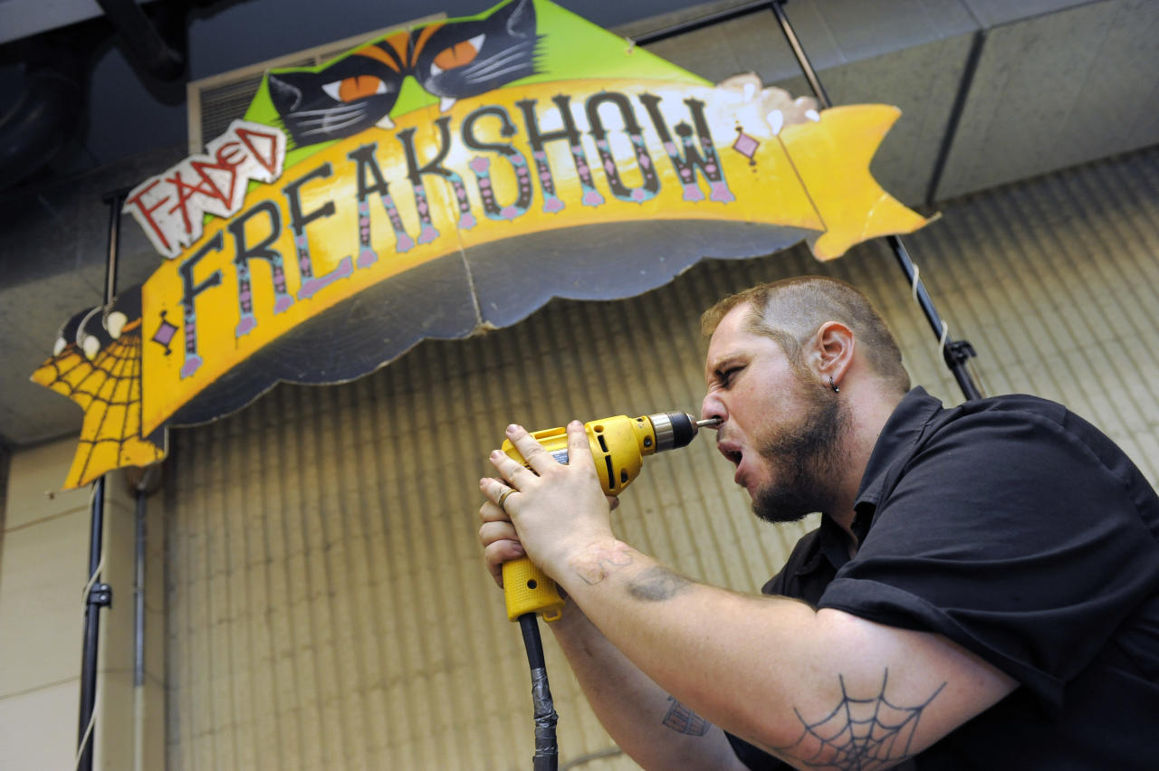 Aaron Woody, 29, of Fort Collins, drills a masonry bit into his face at the freak show at the first Denver County Fair in Denver on Thursday, July 28, 2011. (AP Photo/Chris Schneider)