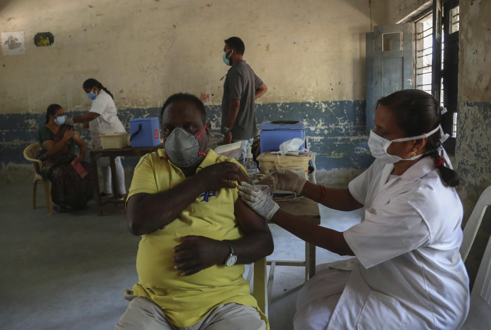 A health worker administers Covishield, Serum Institute of India's version of the AstraZeneca vaccine to a man during a special vaccination drive held in the premises of a government school in Hyderabad, India, Sunday, May 30, 2021. (AP Photo/Mahesh Kumar A.)