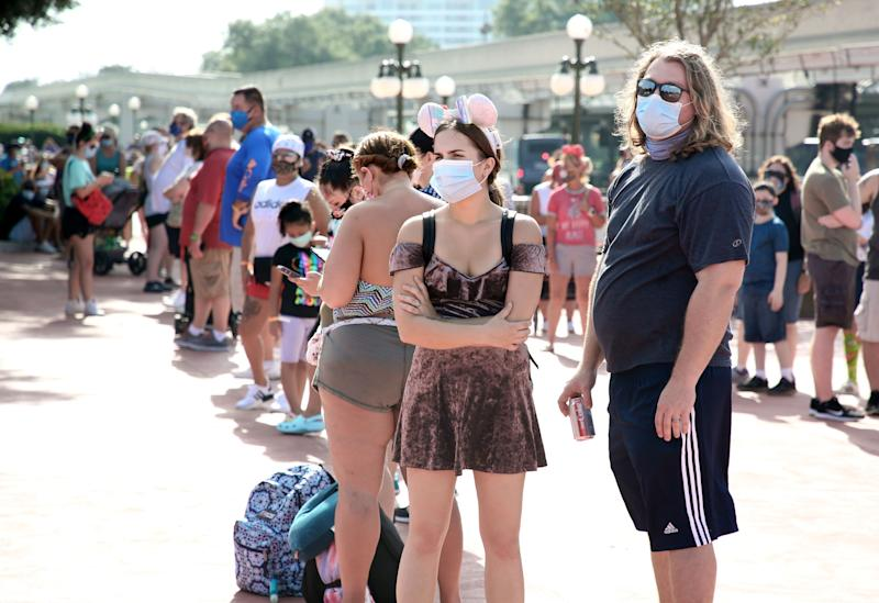 Guests wearing protective masks wait outside the Magic Kingdom theme park at Walt Disney World on the first day of reopening, in Orlando, Florida, on July 11, 2020. - Disney's flagship theme park reopened its doors to the general public on Saturday, along with Animal Kingdom, as part of their phased reopening in the wake of the Covid-19 pandemic. New safety measures have been implemented including mandatory face masks for everyone and temperature checks for guests before they enter. (Photo by Gregg Newton / Gregg Newton / AFP) (Photo by GREGG NEWTON/Gregg Newton/AFP via Getty Images)