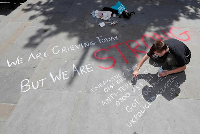<p>A man writes a message on the pavement in central Manchester, Britain on May 23, 2017. (Darren Staples/Reuters) </p>
