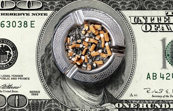 Full ash tray on top of a giant hundred dollar bill.