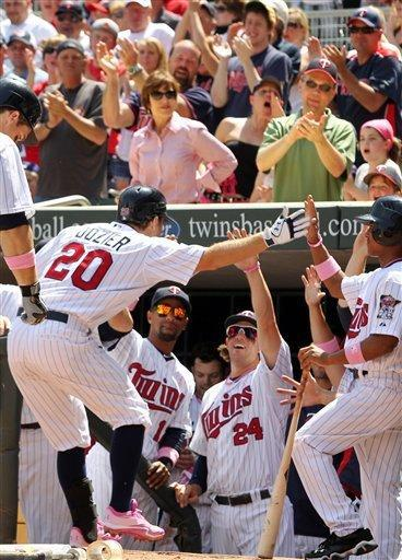 Minnesota Twins' Brian Dozier (20) is congratulated by teammates after hitting a home run against Toronto Blue Jays pitcher Ricky Romero during the third inning of a baseball game on Sunday, May 13, 2012, in Minneapolis. (AP Photo/Genevieve Ross)