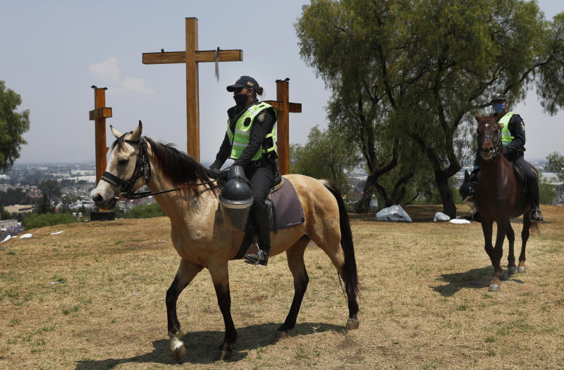 Mounted police guard the La Estrella hill where crosses are located for an annual Holy Week Via Crucis in Iztapalapa, Mexico City, Thursday, April 9, 2020. The area is closed and the police are preventing people from making to the area as a way to help slow down the spread of the new coronavirus. (AP Photo/Marco Ugarte)