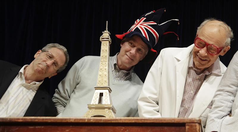 Nobel Prize laureates Eric Maskin, Rich Roberts and Dudley Herschbach lean over behind a mini Eiffel Tower during a performance at the Ig Nobel Prize ceremony at Harvard University, in Cambridge, Mass., Thursday, Sept. 20, 2012. The Ig Nobel prize is an award handed out by the Annals of Improbable Research magazine for silly sounding scientific discoveries that often have surprisingly practical applications. (AP Photo/Charles Krupa)