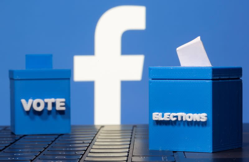 3D printed ballot boxes are seen in front of a displayed Facebook logo