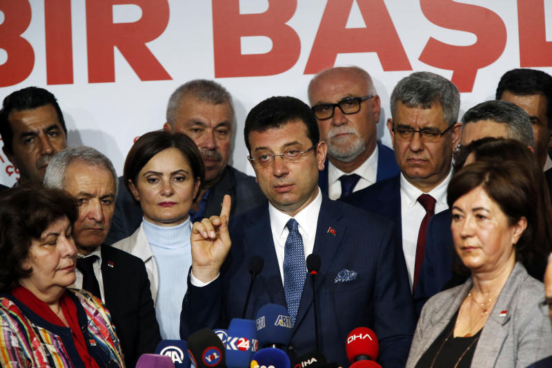 Ekrem Imamoglu, centre, the opposition, Republican People's Party's (CHP) mayoral candidate in Istanbul, talks to members of the media, in Istanbul, Tuesday, April 9, 2019. Turkey's President Recep Tayyip Erdogan's ruling Justice and Development Party, or AKP, says it will seek a re-run of last week's mayoral election in Istanbul, citing alleged irregularities. The party suffered a major setback in the elections. Opposition candidates won in Turkey's capital, Ankara, and squeezed out the ruling party in Istanbul. (AP Photo/Lefteris Pitarakis)
