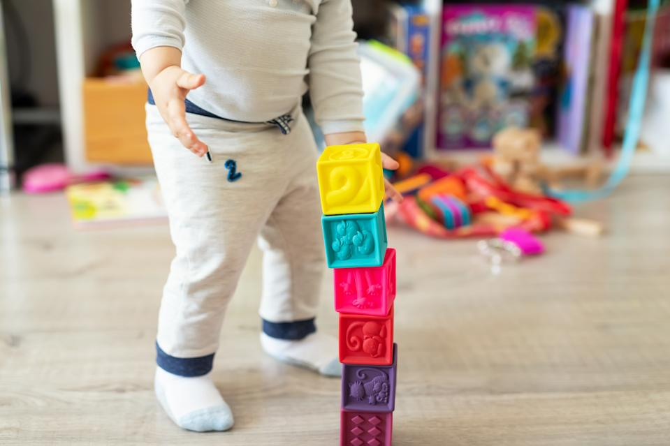 Cute adorable caucasian baby boy playing colorful toys at home. Happy child having fun building tower of soft rubber cubes. Children development and hapy chilldhood concept.