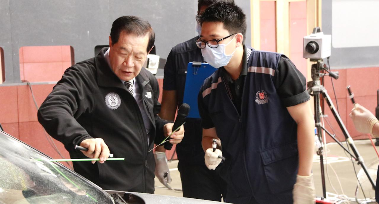 <p>Forensic scientist Dr Henry C. Lee shows one of the course participants how to measure a bullet trajectory.<br /> Photo: Hannah Teoh/Yahoo News Singapore </p>