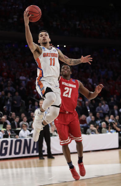 Florida guard Chris Chiozza (11) goes up for a shot against Wisconsin guard Khalil Iverson (21) in overtime of an East Regional semifinal game of the NCAA men's college basketball tournament, Saturday, March 25, 2017, in New York. (AP Photo/Frank Franklin II)