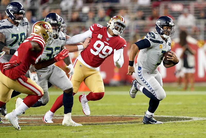 Quarterback Russell Wilson of the Seattle Seahawks scrambles against the defense of the San Francisco 49ers. (Photo by Thearon W. Henderson/Getty Images)