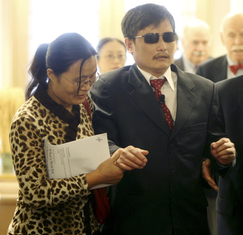 FILE - In this Thursday, May 31, 2012 file photo Chen Guangcheng is helped to the stage by his wife, Yuan Weijung, before speaking at the Council on Foreign Relations in New York. Prominent cases of asylum seekers taking shelter in embassies include blind dissident Chen Guangcheng who escaped house arrest in his Shandong village and sought refuge at the  U.S. embassy in Beijing. He left after six days, and subsequently was allowed to go to New York with his wife and two children. (AP Photo/Seth Wenig, File)