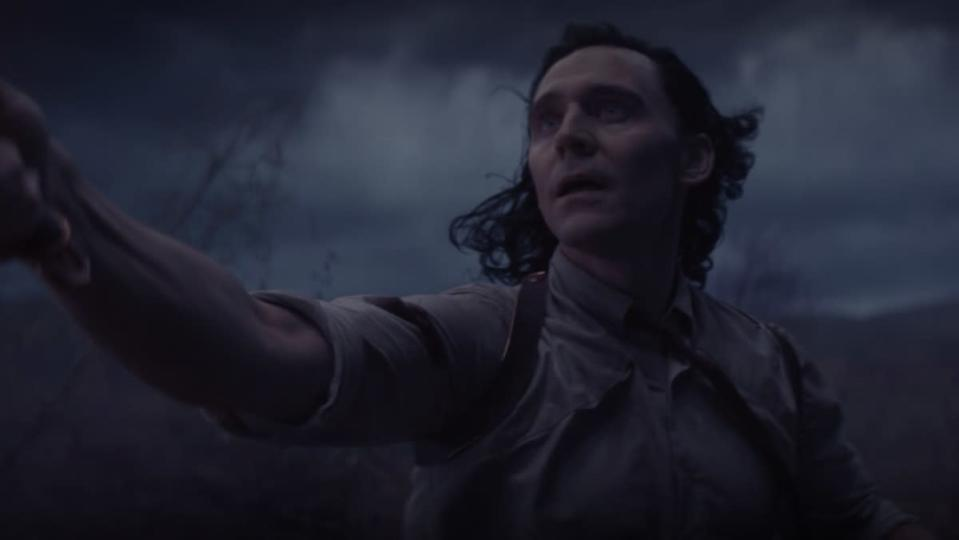 Tom Hiddleston holds a knife and looks to the sky while wearing a dress shirt and tie