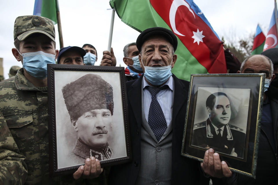 CORRECTING IDENTY OF PORTRAITS TO TURKEY'S FOUNDER MUSTAFA KEMAL ATATURK, LEFT, AND AZERBAIJAN'S LATE PRESIDENT HAYDAR ALIYEV, RIGHT - An Azerbaijani man holds portraits of Turkey's founder Mustafa Kemal Ataturk, left, and Azerbaijan's late president Haydar Aliyev, father of Ilham Aliyev wearing in KGB Gen. Major uniform on the right, as he celebrates the transfer of the Lachin region to Azerbaijan's control, as part of a peace deal that required Armenian forces to cede the Azerbaijani territories they held outside Nagorno-Karabakh, in Aghjabadi, Azerbaijan, Tuesday, Dec. 1, 2020. Azerbaijan has completed the return of territory ceded by Armenia under a Russia-brokered peace deal that ended six weeks of fierce fighting over Nagorno-Karabakh. Azerbaijani President Ilham Aliyev hailed the restoration of control over the Lachin region and other territories as a historic achievement. (AP Photo/Emrah Gurel)