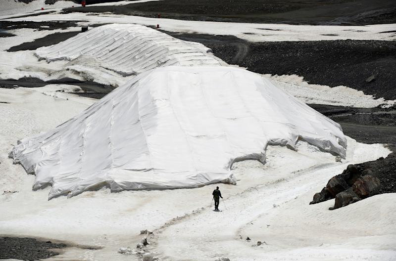 A person walks next to covered depots of snow to outlast the summer in a glacier ski resort near the village of St. Leonhard im Pitztal, Austria. (Photo: Lisi Niesner/Reuters)