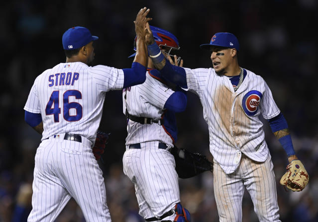 Chicago Cubs closing pitcher Pedro Strop left, celebrates with teammate Javier Baez right, while catcher Victor Caratini back, looks on after defeating the Colorado Rockies 6-3 during a baseball game Tuesday, June 4, 2019, in Chicago. (AP Photo/Paul Beaty)