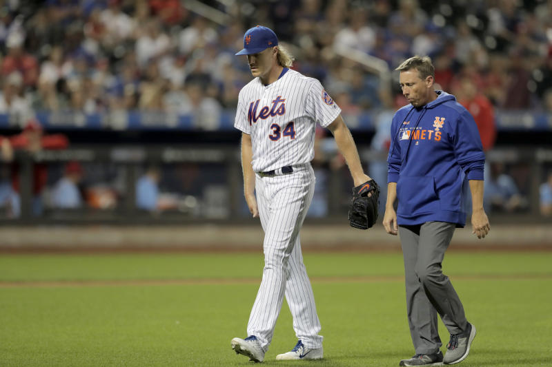 New York Mets starting pitcher Noah Syndergaard (34) touches his leg as he walks with a trainer while leaving the baseball game against the St. Louis Cardinals during the seventh inning Saturday, June 15, 2019, in New York. (AP Photo/Julio Cortez)