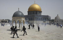 Palestinians run from sound grenades thrown by Israeli police in front of the Dome of the Rock in the al-Aqsa mosque complex in Jerusalem, Friday, May 21, 202, as a cease-fire took effect between Hamas and Israel after a 11-day war. (AP Photo/Mahmoud Illean)