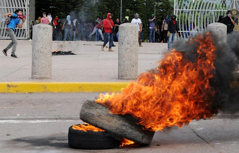 Students from the National Autonomous University of Honduras (UNAH) burn tyres during a protest in Tegucigalpa on November 4, 2015 (AFP Photo/Orlando Sierra)
